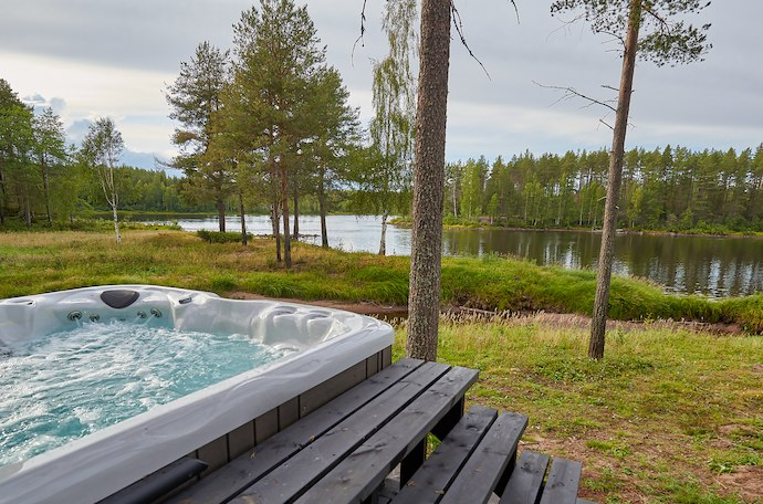 Enjoy an outdoor jacuzzi overlooking the river at an Arctic spa